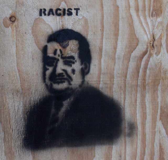 Her en der (soms op gevels van privéwoningen) duikt graffiti op waarin vooral Karim Van Overmeire geviseerd wordt…