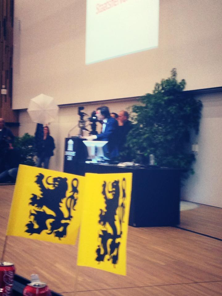 Di Rupo, eerste nar van België, spreekt de studenten toe. De Vlaamse Leeuwen moet hij er maar bijnemen.