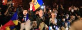 Romanian presidential candidate Klaus Iohannis waves as he celebrates his victory in the election run-off, with protesters in central Bucharest