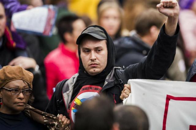 """AFA leider in Gouda naast het AFA spandoek. Terwijl er gescandeerd werd: """"Zwarte piet bestaat niet!"""""""
