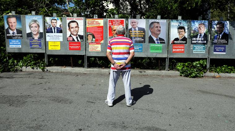 FILE PHOTO: A man looks at campaign posters of the 11th candidates who are running in the 2017 French presidential election, in Saint Andre de La Roche